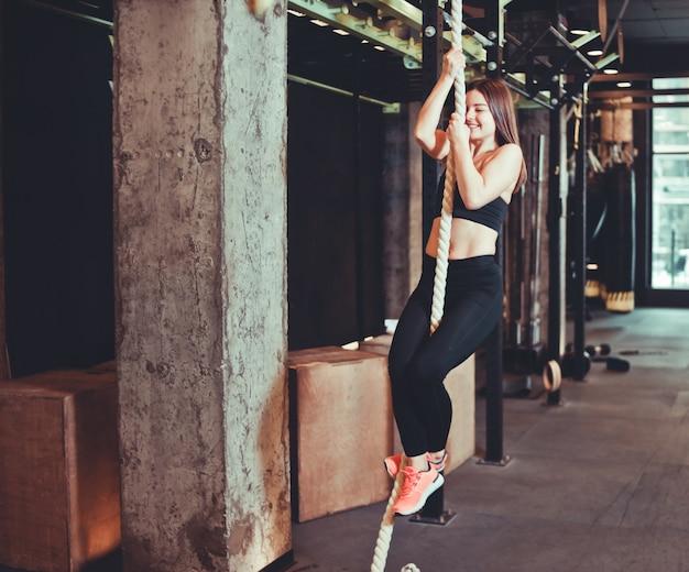Monter la fille grimper sur la corde au gymnase.