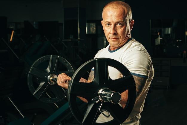 Monter un homme âgé soulevant des haltères dans une salle de sport