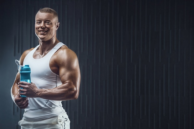 Monter l'homme à l'entraînement en salle de sport avec shaker sur fond sombre
