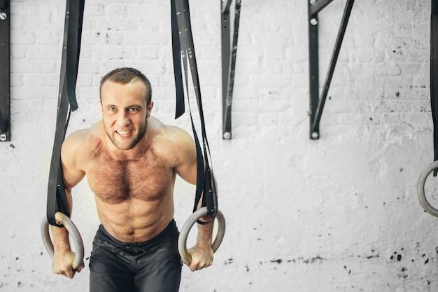 Monter l'homme tirant sur des anneaux de gymnastique.