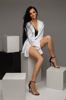 Monter une jeune femme brune portant une chemise avec des jambes nues, assise sur des cubes noirs et blancs sur fond gris, espace de copie. photo de haute qualité