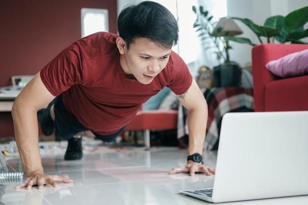Monter un jeune homme faisant du yoga sur une planche et regardant des didacticiels en ligne sur un ordinateur portable, s'entraînant dans le salon