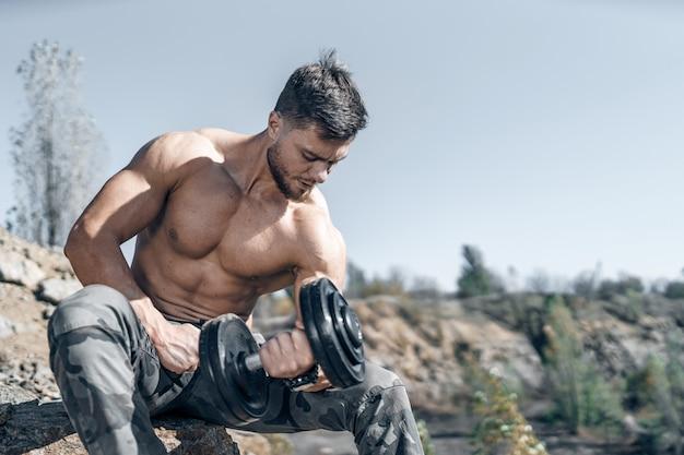 Monter un jeune homme soulevant des haltères faisant de l'exercice en plein air. sport, fitness, haltérophilie, musculation, entraînement, athlète, concept d'exercices d'entraînement. vue de côté.