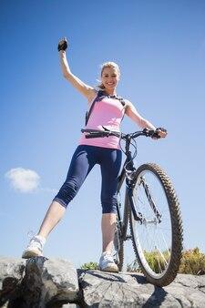 Monter jolie cycliste sur un terrain rocheux, souriant à la caméra