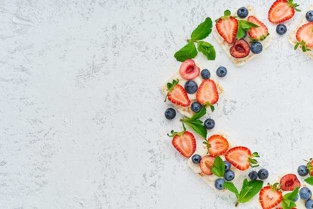 Montez le cadre de pain croustillant avec des baies et des fruits concept coloré sur la vue de dessus de l'espace de copie fond pastel