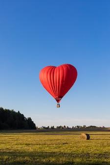 Montgolfière en forme de coeur rouge survolant les champs avec des meules de foin