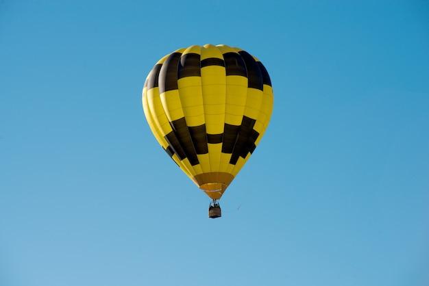 Montgolfière noire et jaune dans un ciel bleu