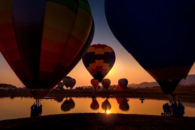 Montgolfière silhouette sur paysage de lac de montagnes au coucher du soleil