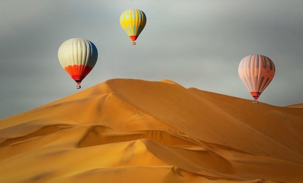 Montgolfières colorées survolant les dunes de sable au coucher du soleil