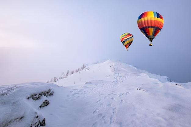 Montgolfières colorées volant sur la colline de neige avec blizzard