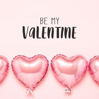 Montgolfières roses en forme de coeur sur une surface rose. concept pour la saint valentin