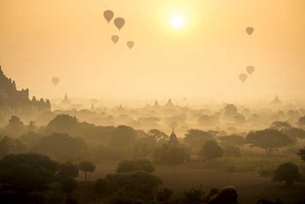 Les montgolfières de la scène sunrise survolent le champ de la cité antique de la pagode à bagan, au myanmar.