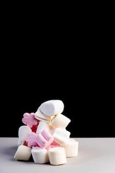 Monticule de nuages de sucre blanc et rose sur fond noir
