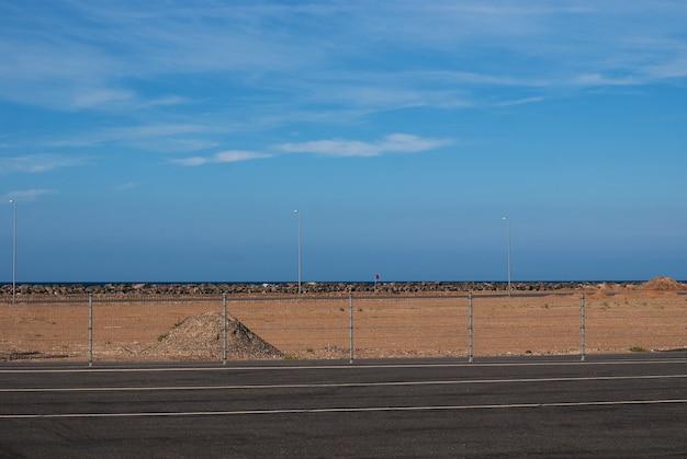 Un monticule de sable rouge sur fond de ciel bleu près de la route