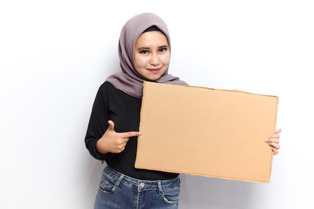 Montrant une affiche vierge pour l'inscription et le texte de jeunes belles femmes asiatiques musulmanes s'habillent en hijab