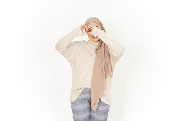 Montrant le coeur ou l'amour signe de belle femme asiatique portant le hijab isolé sur fond blanc