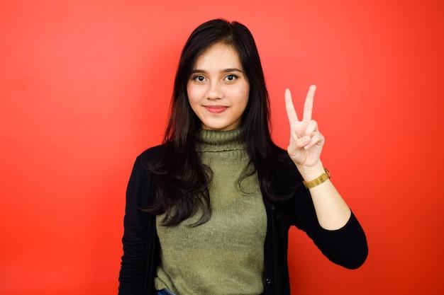 Montrant deux doigts de jeunes belles femmes asiatiques utilisant un pull noir avec fond isolé rouge