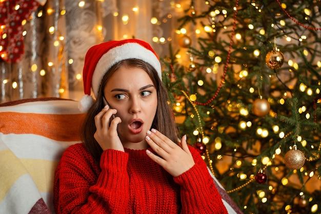 Montrant des émotions tout en parlant au téléphone, expression faciale lumineuse de surprise et d'indignation