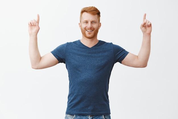 Montrant fièrement un grand concept vers le haut. portrait de beau mec européen confiant et heureux avec des poils, levant les mains et pointant vers le haut avec une expression heureuse et satisfaite, se sentant bien