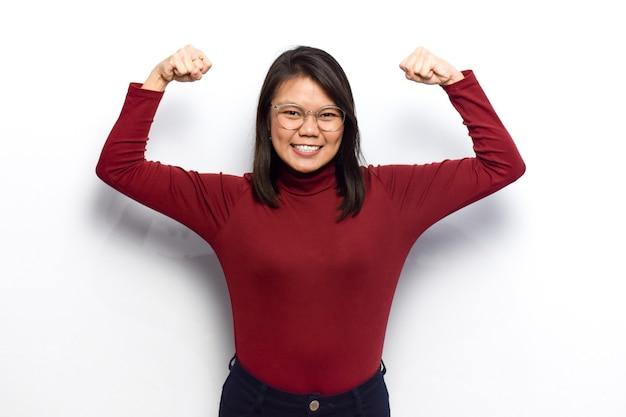 Montrant la force et levez les bras de jeunes belles femmes asiatiques s'habillent d'une chemise rouge isolée sur blanc