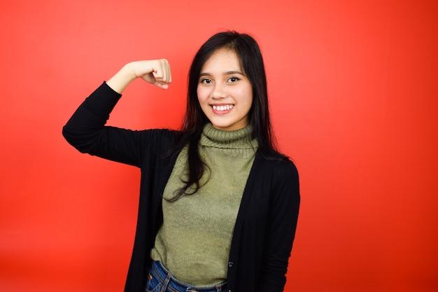 Montrant la force et souriant de jeunes belles femmes asiatiques utilisant un pull noir isolé sur rouge