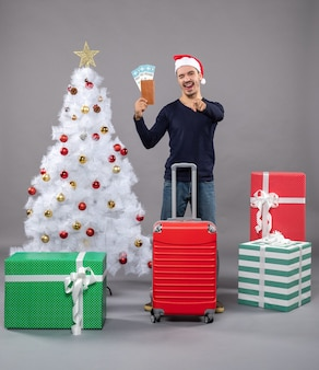 Montrant la langue homme avec valise rouge montrant ses billets de voyage autour de l'arbre de noël blanc et présente sur fond gris
