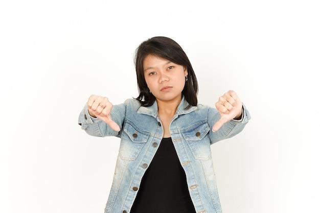 Montrant les pouces vers le bas de la belle femme asiatique portant une veste en jean et une chemise noire isolée sur blanc