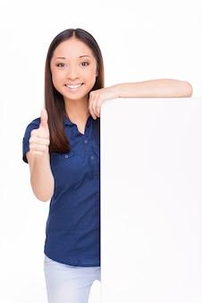 Montrant son pouce vers le haut. joyeuse jeune femme asiatique regardant la caméra et montrant son pouce vers le haut