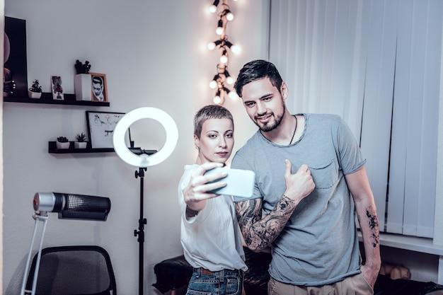 Montrant le travail terminé. beaming client du salon de tatouage montrant la vignette et étant satisfait lors de la photographie