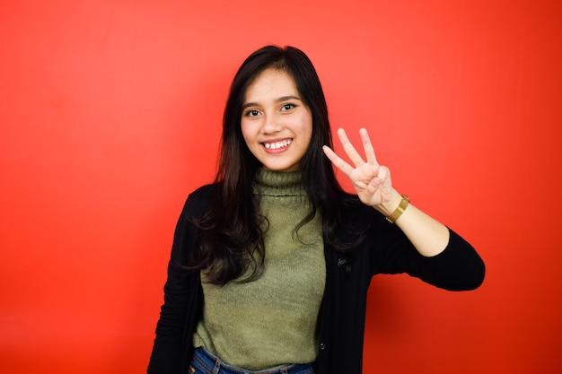 Montrant trois doigts de jeunes belles femmes asiatiques utilisant un pull noir isolé sur rouge