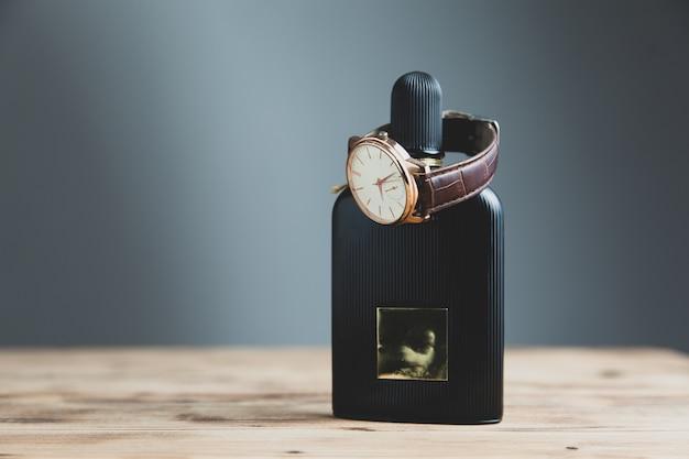 Montre et bouteille de parfum sur le bureau