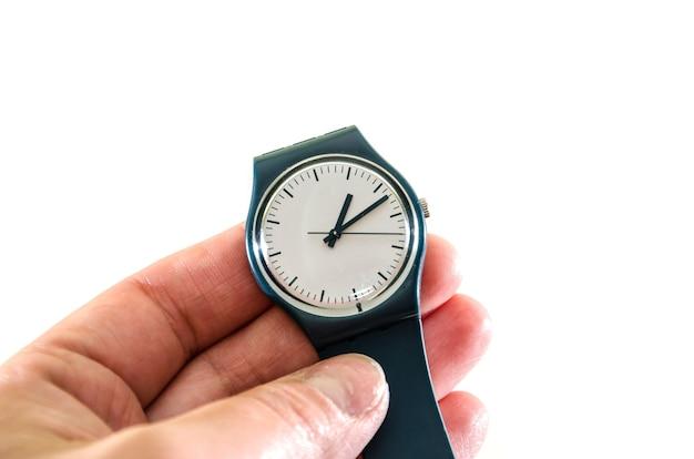 Montre-bracelet à la main sur blanc