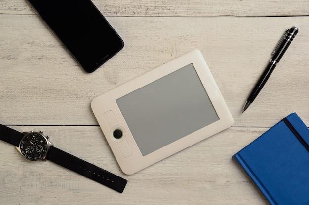 Montre-bracelet mécanique, agenda, e-book, téléphone portable et stylo se trouvent sur une table lumineuse en bois