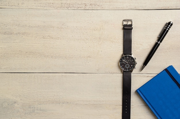 Une montre-bracelet mécanique, un agenda et un stylo se trouvent à droite sur une table en bois clair
