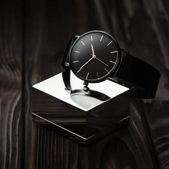 Montre-bracelet moderne noire sur cube de chrome avec bague en or sur fond de bois