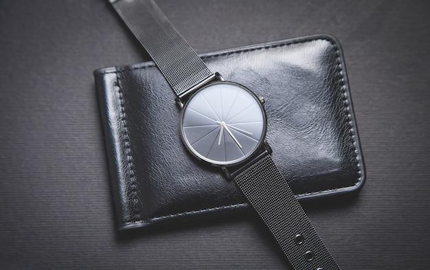 Montre bracelet noire et portefeuille en cuir noir sur fond noir
