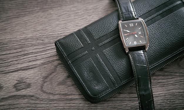 Montre-bracelet et portefeuille noirs sur le bureau.