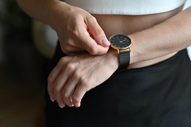 Montre-bracelet pour femme en or sur la main de la jeune fille