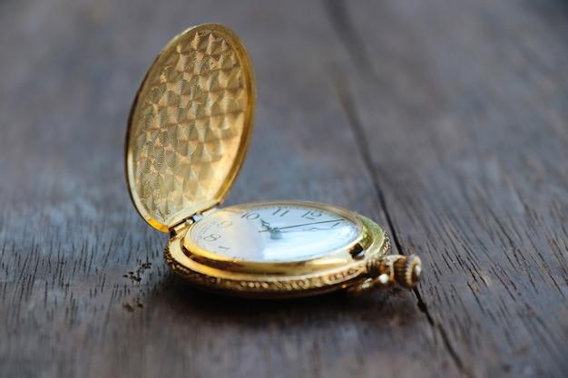 Montre classique de style pocketwatch doré, 10 h 00 sur fond de table en bois
