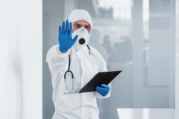 Montre le geste d'arrêt à la main. homme médecin scientifique en blouse de laboratoire, lunettes défensives et masque tenant le bloc-notes dans les mains
