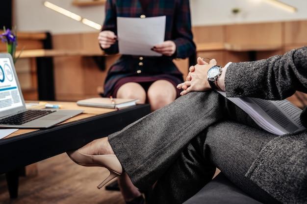Montre. gros plan d'une femme d'affaires prospère portant une montre à main parlant au secrétaire