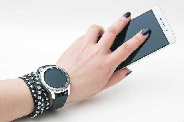 Montre intelligente sur la main avec un smartphone, isolé sur fond blanc.