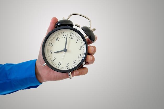 Une montre à la main indique qu'il est temps de travailler.