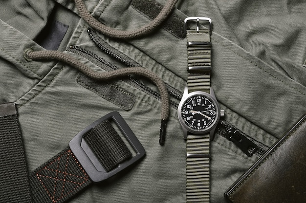 Montre militaire vintage avec bracelet nato et ceinture tactique sur fond vert armée, montre-bracelet mécanique classique, mode et accessoires pour hommes militaires.