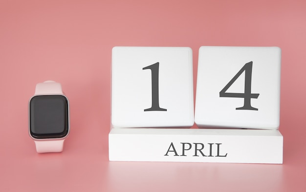 Montre moderne avec calendrier cube et date 14 avril sur fond rose. concept vacances au printemps.