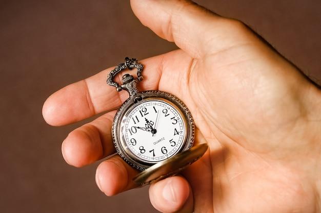 Une montre de poche entre les mains d'un homme