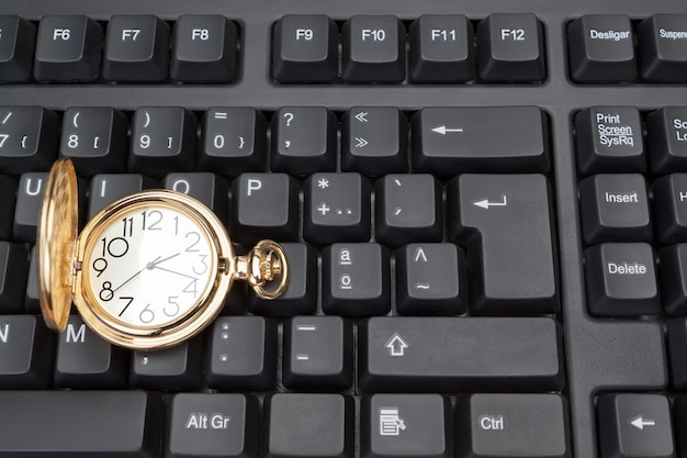 Montre de poche en or sur fond de clavier d'ordinateur.