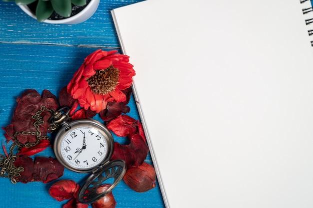 Montre de poche vintage dorée posée sur une table en bois bleue avec un cahier vierge