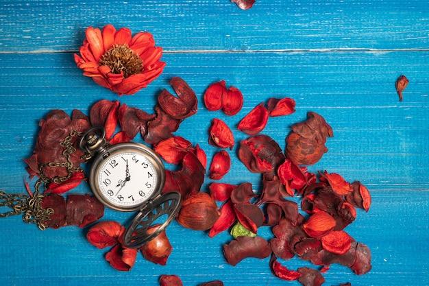 Montre de poche vintage dorée posée sur une table en bois bleue avec des fleurs séchées rouges aux arômes