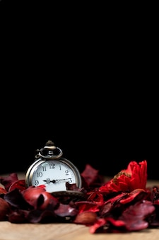 Montre de poche vintage dorée posée sur une table en bois avec des fleurs séchées rouges à l'arôme